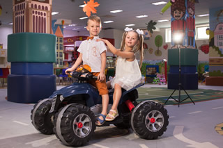 Мальчик и девочка в ортопедических детских босоножках Ортофут на квадроцикле магазине детской ортопедической обуви в Киеве